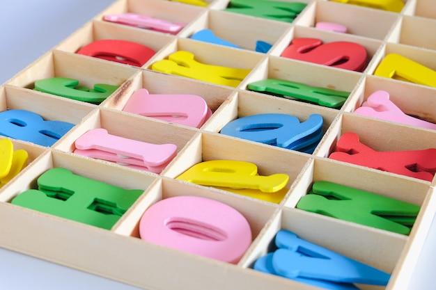 Lettere dell'alfabeto in diversi colori per la decorazione dei bambini in scatola di legno.