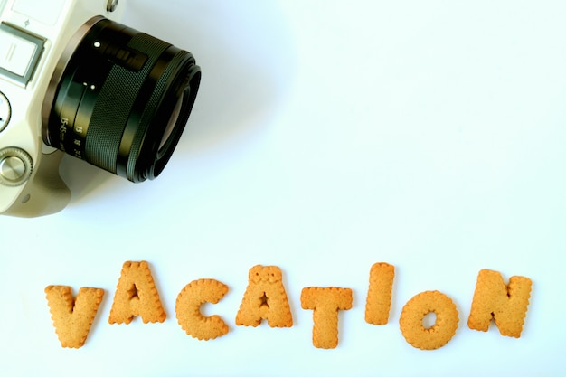 Biscotti a forma di alfabeto che compitano la parola vacanza con una macchina fotografica sulla tavola blu-chiaro