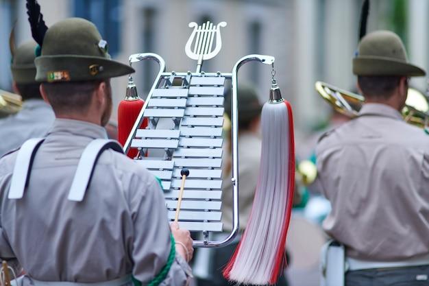 Banda alpina con bell lyra in marcia durante un raduno nazionale del corpo degli alpini
