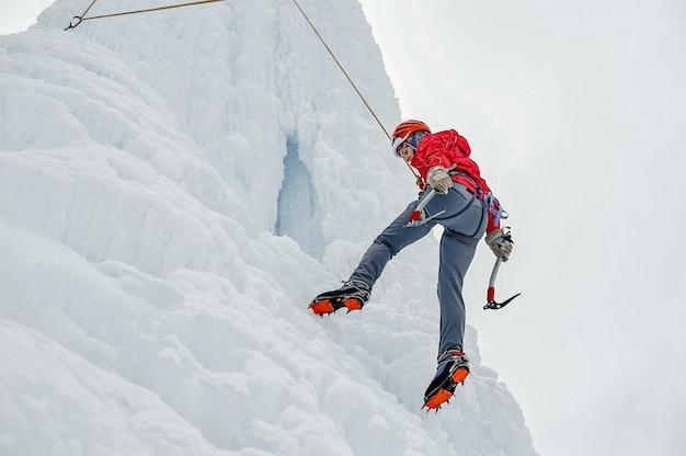 Donna alpinista con ascia di attrezzi da ghiaccio in casco arancione che scala una grande parete di ghiaccio. ritratto di sport all'aria aperta