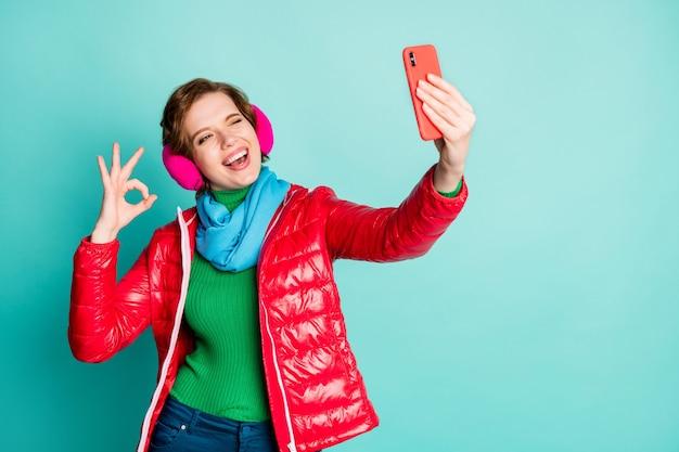 Tutto a posto! foto di divertente bella signora tenere il telefono facendo selfie occhi ammiccanti che mostra okay simbolo indossare sciarpa cappotto rosso paraorecchie rosa pantaloni jumper isolato teal parete di colore