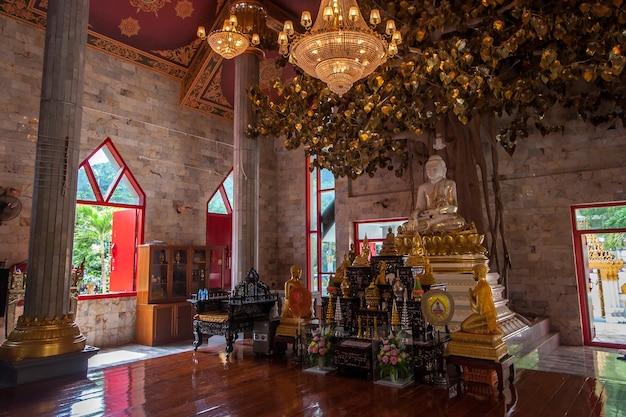 Altare con statua di buddha e altre decorazioni nel tempio buddista. albero dei desideri e grandi lampadari luminosi.
