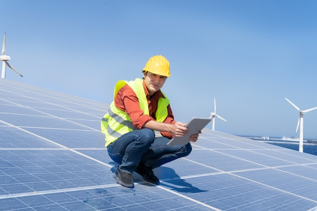 Concetto di energia alternativa - ingegnere seduto su pannelli solari, energia verde e concetto di industria eco friedly