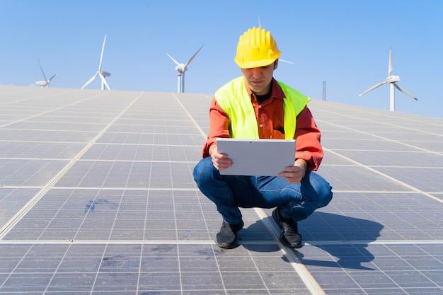 Ingegnere del concetto di energia alternativa che si siede sui pannelli solari, sull'energia verde e sul concetto di industria di eco friedly