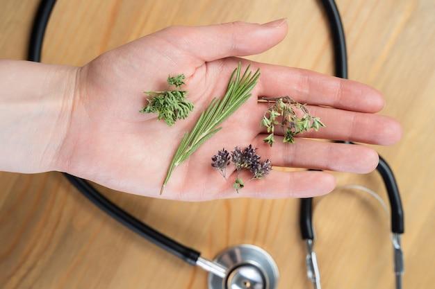 Assistenza sanitaria alternativa a base di erbe fresche e capsula in mano del medico su sfondo bianco.
