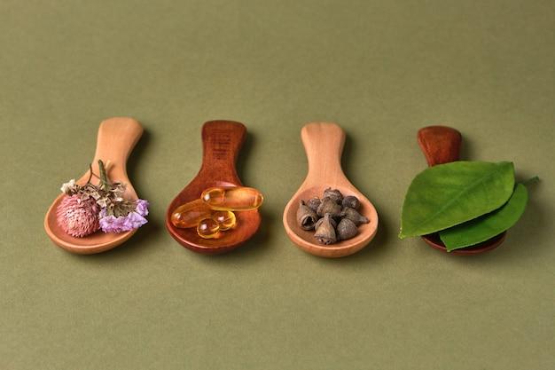 Medicina alternativa e a base di erbe in cucchiai di legno su sfondo verde oliva