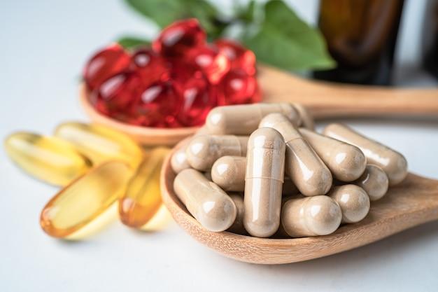 Capsula organica a base di erbe di medicina alternativa con vitamina e olio di pesce omega 3, minerale, farmaco con integratori naturali di foglie di erbe per una vita sana e buona.