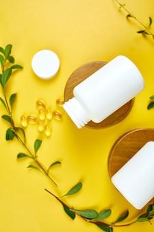 Capsula organica a base di erbe di medicina alternativa con vitamina e, olio di pesce omega tre con foglie verdi, concetto di assistenza sanitaria, cibo sano