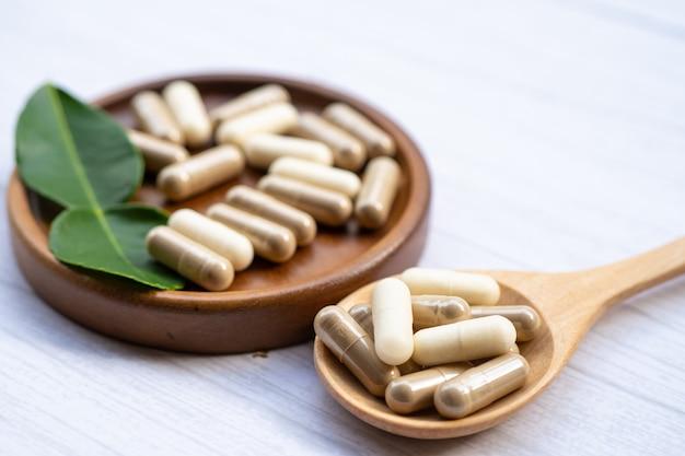 Capsule organiche a base di erbe di medicina alternativa con minerali vitaminici, farmaci con integratori naturali di foglie di erbe per una vita sana