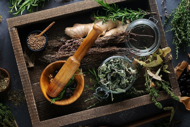 Medicina alternativa, trattamento a base di erbe mortaio di legno, menta, tiglio, timo, lavanda su uno sfondo scuro, vista dall'alto.
