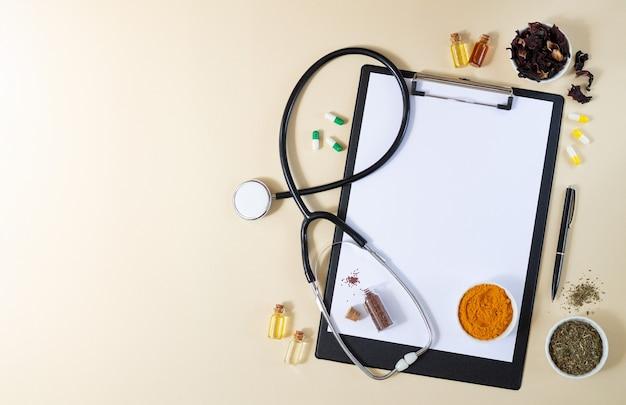 Medicina alternativa, naturopatia o concetto di ayurveda. appunti in bianco con lo stetoscopio, varie erbe curative, spezie, capsule e oli sani sulla vista superiore del tavolo beige