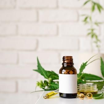 Medicina alternativa, cosmetici naturali. olio di cbd e foglie di cannabis cosmetici vista frontale, copia spazio, mock up design