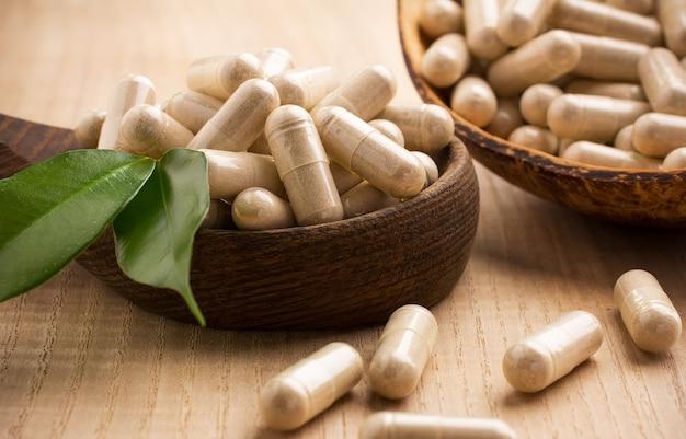 Compresse di medicina alternativa su un cucchiaio di legno, foglia verde.