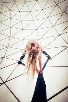 Punto di vista alternativo di bella ragazza caucasica bionda che fa gli esercizi di spettacolo di sport di circo aereo con cielo bianco