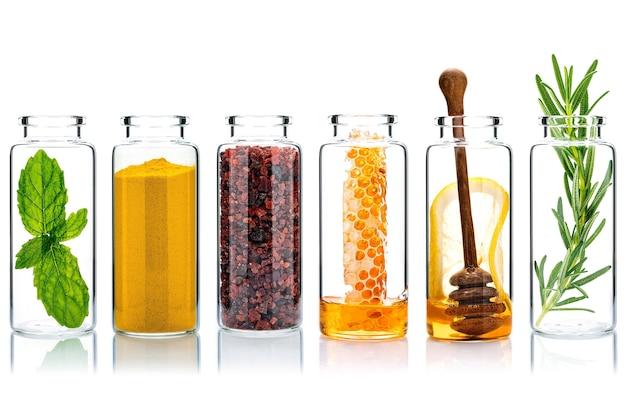 Cura della pelle alternativa con ingredienti naturali in bottiglie di vetro isolare su sfondo bianco.
