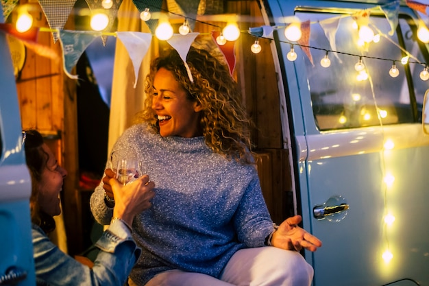 Concetto alternativo di viaggio e celebrazione con un paio di persone adulte allegre donne felici festeggiano insieme in un camper vintage e luci di festa all'aperto