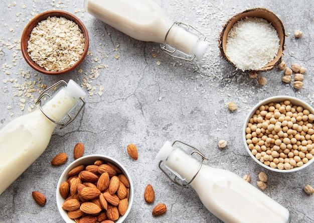 Tipi alternativi di latte vegano in bottiglie di vetro su una superficie di cemento