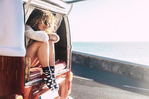 Modo alternativo di viaggiare e godersi il mondo. scopri nuovi posti e vivi con vista sull'oceano dalla finestra. felice bella femmina seduta fuori da un furgone classico e guardando il mare. rilassati e posi