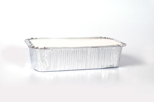 Scatola per alimenti in alluminio su sfondo bianco.
