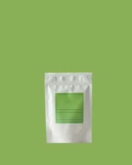 Sacchetto di alluminio per tè e caffè con etichetta verde per la firma su sfondo verde
