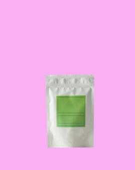 Bustina in alluminio per tè e caffè con etichetta verde per firma su sfondo rosa