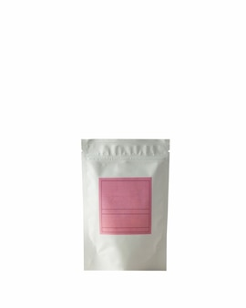 Bustina in alluminio per tè e caffè con etichetta rosa per firma su sfondo bianco
