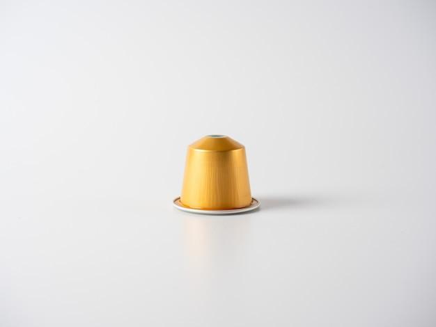 Capsula di alluminio di colore dorato con caffè macinato per la macchina da caffè su sfondo bianco.