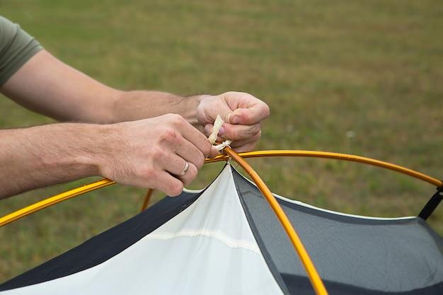Archi di montaggio in alluminio per l'installazione di una tenda gialla turistica nel primo piano della mano. attrezzatura leggera per il turismo. attività all'aperto, istruzioni di montaggio, ecoturismo domestico. copia spazio