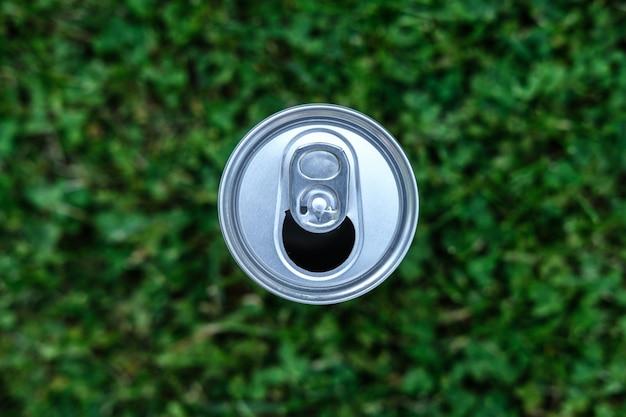 Lattina aperta in alluminio da soda, vista dall'alto su uno sfondo di erba in giardino.