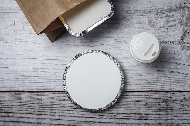 Contenitori per alimenti da asporto in alluminio preparati per la consegna in sacchetti di carta riciclabili. lay piatto