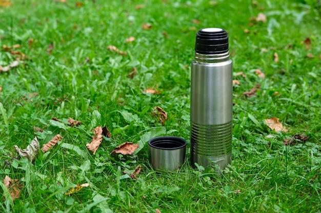 Un thermos di alluminio e una tazza termica stanno fianco a fianco su un prato con erba e foglie autunnali secche sparse raramente.