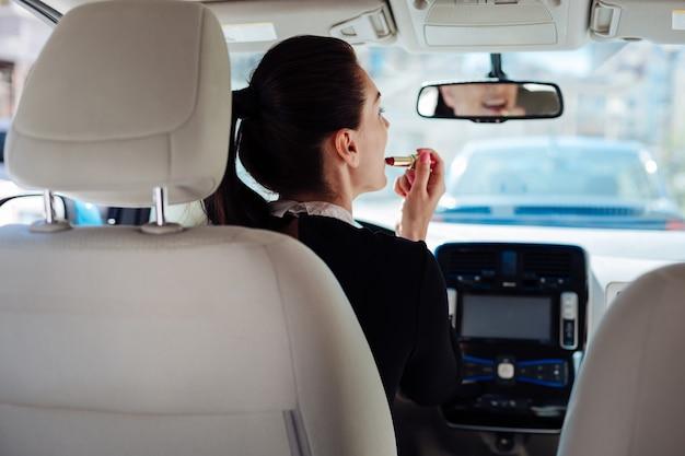 Sempre bella. attraente bella bella donna che guarda nello specchietto retrovisore e tiene un rossetto mentre lo indossa