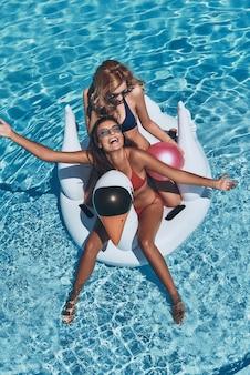 Sempre felici insieme. vista dall'alto di due belle giovani donne in bikini che sorridono mentre galleggiano su un grande cigno gonfiabile