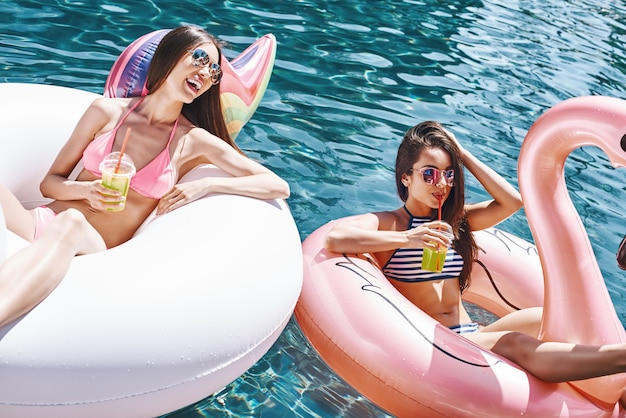 Sempre felici insieme due giovani donne carine e felici in costume da bagno che bevono arancia fresca mentre