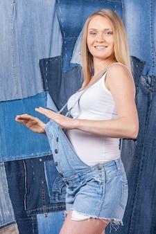 Sempre alla moda. vista laterale della bella donna incinta in jeans vestiti in posa mentre si sta in piedi sullo sfondo dei jeans