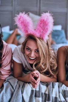 Sempre in vena di divertimento! attraente giovane donna con orecchie da coniglio rosa che sorride e guarda la telecamera mentre è sdraiata sul letto