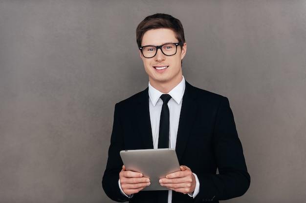 Sempre pronto ad aiutarti. fiducioso giovane in abiti da cerimonia che tiene tablet digitale e sorride mentre si trova in piedi su sfondo grigio gray