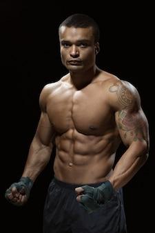 Sempre pronto. studio shot di un forte combattente in posa in studio mostrando il suo torso tonico