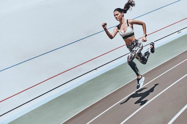 Sempre in forma. vista dall'alto della giovane donna in abbigliamento sportivo che salta