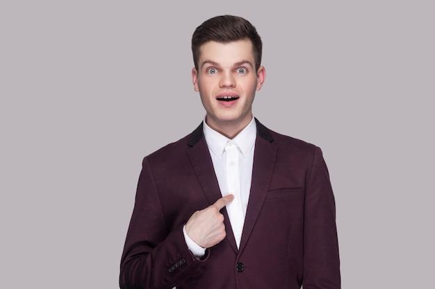 Sono vincitore?! ritratto di bel giovane stupito in abito viola, camicia bianca, in piedi, guardando la telecamera, indicandosi con la faccia sorpresa e chiedendo. girato in studio, isolato su sfondo grigio.