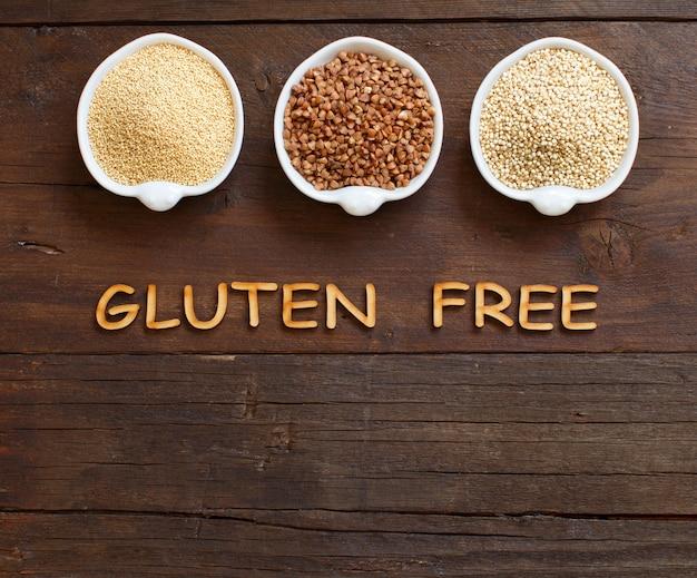Amaranto, grano saraceno e quinoa in ciotole su un tavolo di legno