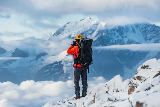 Un fotografo dilettante alpinista con un grande zaino sulle spalle cattura la vista di bellissime montagne innevate con ghiacciai sulla fotocamera.montagna