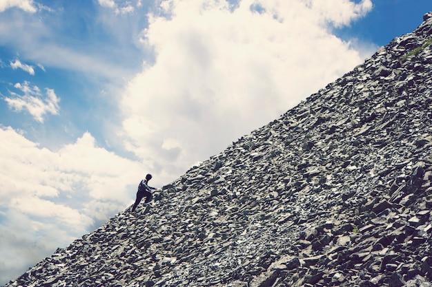 Alpinismo amatoriale contro il cielo azzurro con nuvole. uomo che sale su per la collina per raggiungere la vetta della montagna. persistenza, determinazione, forza, raggiungimento dei concetti target. alluvione di pietra.