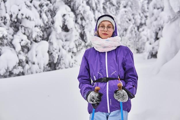Ragazza sciatrice amatoriale cammina nella foresta innevata d'inverno