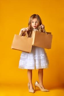 Bambino attraente stupito in vestito e grandi scarpe che tengono i sacchetti della spesa