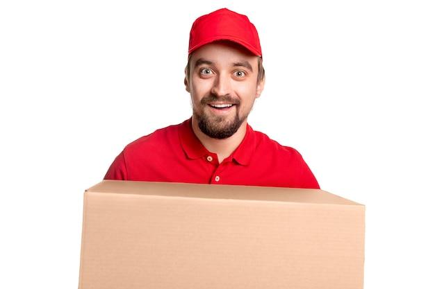 Stupito maschio di consegna barbuto in camicia rossa e berretto che trasporta un'enorme scatola di cartone e guarda con un'espressione del viso eccitata, mentre consegna il pacco