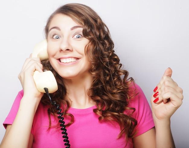 Bella donna riccia stupita che parla sul telefono vintage bianco isolato su sfondo bianco