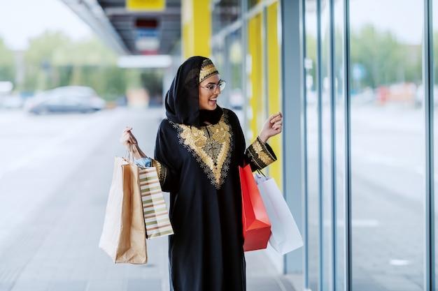 Bella donna musulmana stupita in abbigliamento tradizionale in piedi all'aperto con le borse della spesa in mano e guardando la finestra del negozio.