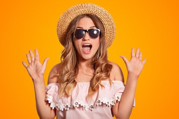 Bellissima giovane femmina europea stupita con cappello estivo, occhiali da sole alla moda e camicetta alla moda, stringe le mani
