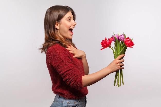 Ragazza bruna stupita che dà un mazzo di fiori o accetta le congratulazioni per le vacanze di primavera